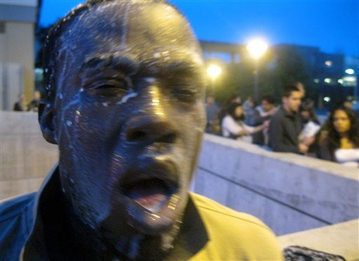 Nnaemeka Alozie, campaign manager for Steinman, reacts with milk on his face after being sprayed with pepper spray during a protest on Tuesday, April 3, 2012, in Santa Monica, Calif. (AP Photo/Courtesy David Steinman)