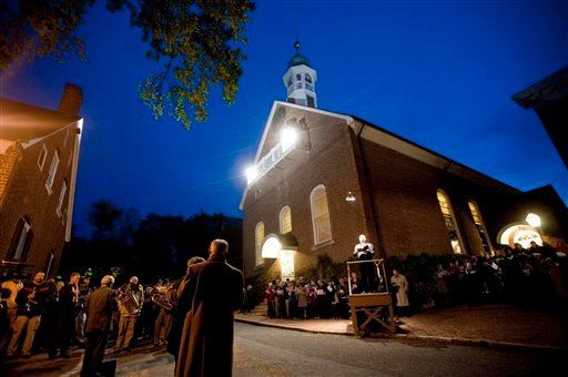 A crowd gathers in front of Home Moravian Church on Salem Square in Winston-Salem, N.C., for the Easter sunrise service Sunday, April 8, 2012. (AP Photo/Winston-Salem Journal, Lauren Carroll)