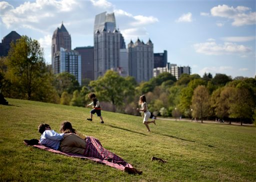 FILE - In this March 25, 2012, file photo a couple enjoy a sunny afternoon against the backdrop of the Midtown skyline from Piedmont Park in Atlanta. (AP Photo/David Goldman)