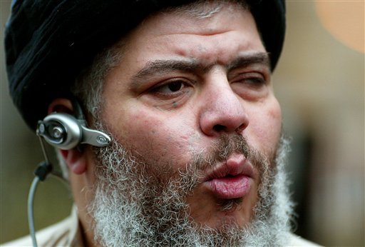 In this Jan. 23, 2004 file photo, self-styled cleric Abu Hamza al-Masri leads his followers in prayer in a street outside Finsbury Park Mosque, on the first anniversary of its closure by anti-terrorism police, London. (AP)