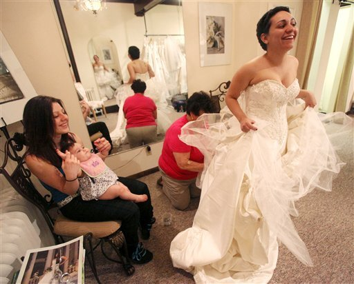 In this April 8, 2010 photo, Jessica Vega, right, tries on the wedding gown at Bella Coutre, in Newburg, N.Y. (AP Photo/Times Herald-Record, Jeff Goulding)
