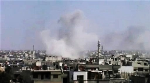 In this image made from amateur video released by the Syrian Media Council and accessed Tuesday, April 10, 2012, smoke rises following purported shelling in Homs, Syria. (AP Photo/Syrian Media Council via AP video)