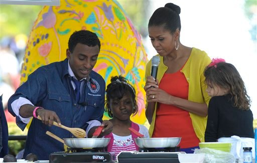 First lady Michelle Obama helps make tacos with chef Marcus Samuelsson during the annual White House Easter Egg Roll, Monday, April 9, 2012, on the South Lawn of the White House in Washington. (AP Photo/Susan Walsh)