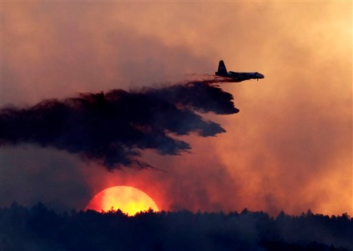 FILE -- In this Sept. 12, 2010 file photo, a slurry bomber drops retardant on a burning ridge as the sun sets behind it as a wildfire burns near Loveland, Colo. (AP Photo/Ed Andrieski, File)
