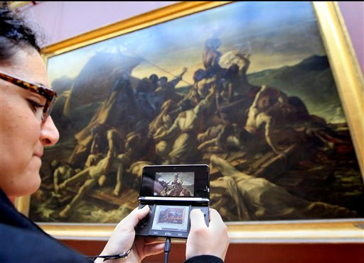 """A visitor studies a painting """"The Raft of the Medusa"""" by French artist Theodore Gericault 1791 - 1824 with the help of the new audio guide at the Louvre Museum in ParisThursday April 12, 2012. (AP Photo/Jacques Brinon)"""