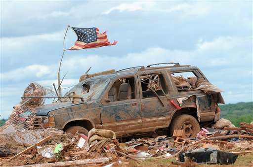 A tattered American flag flies over a vehicle where two young girls ages 5 and 7 were found after a severe thunderstorm spawned a massive tornado at Hideaway Mobile Home Villa in Woodward, Oklahoma April 15, 2012.(AP Photo/ENID NEWS, EAGLE, BONNIE VCULEK)
