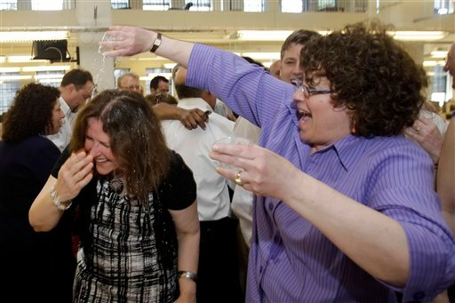 The Philadelphia Inquirer's Susan Snyder, left, has a drink poured on her in celebration by Carolyn Davis after the paper won the Pulitzer Prize for public service, Monday, April 16, 2012, in Philadelphia. (AP Photo/Matt Slocum)