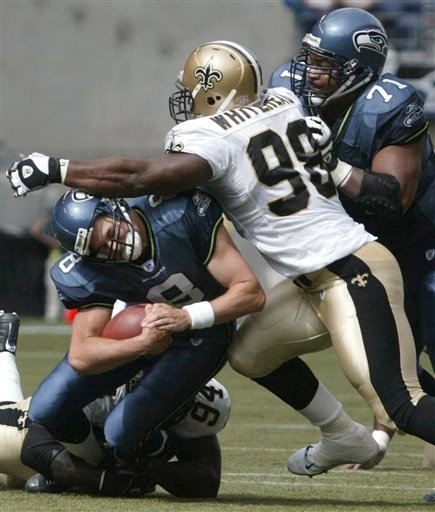 In this Sept. 7, 2003, file photo, Seattle Seahawks quarterback Matt Hasselbeck is sacked by New Orleans Saints defenders Charles Grant (94) and Willie Whitehead (98) during an NFL football game in Seattle.