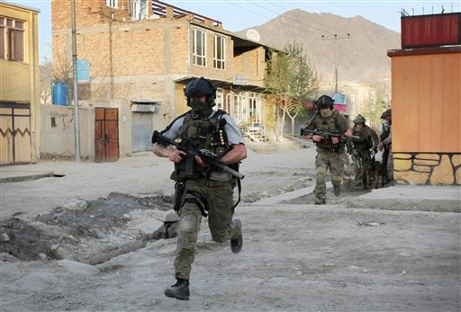 In an April 15, 2012 file photo NATO soldiers run during a gun battle in Kabul, Afghanistan. (AP Photo/Musadeq Sadeq/file)
