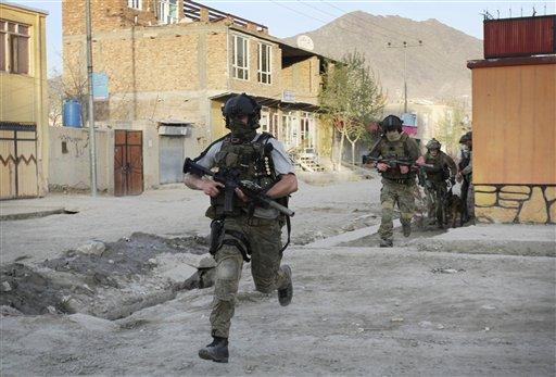 In an April 15, 2012 file photo NATO soldiers run during a gun battle in Kabul, Afghanistan. (AP Photo/Musadeq Sadeq/file)