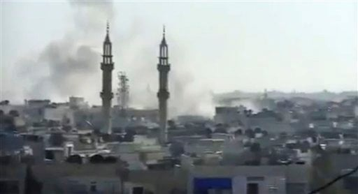 This image made from amateur video released by the Shaam News Network and accessed Tuesday, April 17, 2012, purports to show smoke rising from buildings in Homs, Syria. (AP Photo/Shaam News Network via AP video)