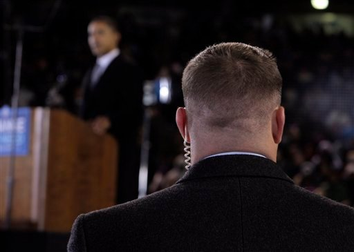 A Secret Service agent stands near then presidential candidate Barack Obama at a rally in Norfolk, Va. The Secret Service forced out three agents April 18, 2012 in a prostitution scandal that has embarrassed President Obama. (AP Photo/Jae C. Hong, File)