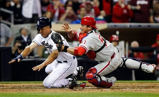 Philadelphia Phillies catcher Carlos Ruiz holds on to the ball after colliding at home plate with San Diego Padres' Will Venable.