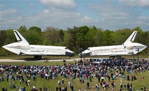 In this photo provided by the Smithsonian Institution via NASA, space shuttles Enterprise, left, and Discovery meet nose-to-nose at the beginning of a transfer ceremony at the Smithsonian's Steven F. Udvar-Hazy Center.