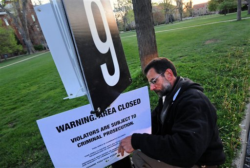 A man posts an area closure sign on the Norlin Quad of the University of Colorado Boulder campus on Friday, April 20, 2012.