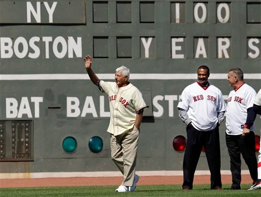 Former Boston Red Sox player Carl Yastrzemski waves to fans as fellow former left fielders Jim Rice left, and Bernie Carbo look on at Fenway Park in Boston, Friday, April 20, 2012, during a celebration of the 100th anniversary of the first regular-season