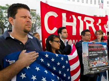 Raul Murrillo director of Hermandad Mexicana Nacional, far left, joins the Coalition for Humane Immigrant Rights of Los Angeles (CHIRLA) during a vigil outside Los Angeles Federal court April 24, 2012. (AP Photo/Damian Dovarganes)