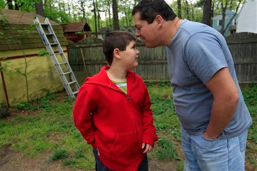 Stuart Chaifetz kisses his son Akian Chaifetz, 10, on the head as they play in the backyard of their home in Cherry Hill, N.J., Wednesday, April 25, 2012. (AP Photo/Mel Evans)