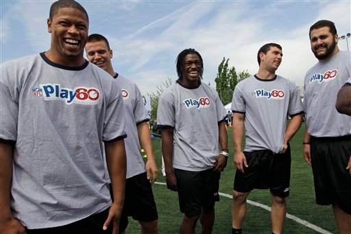 Nick Perry, left, Ryan Tennehill, Robert Griffin III, center, Andrew Luck, second from right, and Matt Kalil laugh during the NFL Play 60 Youth Football Festival, Wednesday, April 25, 2012, in New York.