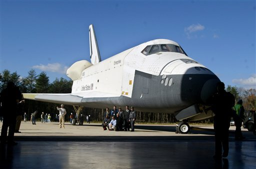 FILE- In this Nov. 20, 2003 file photo, workers pose in front of the Space Shuttle Enterprise prior to moving it into the new Steven F. Udvar-Hazy Center at Dulles Airport in Chantilly, Va. (AP Photo/Lisa Nipp, File)