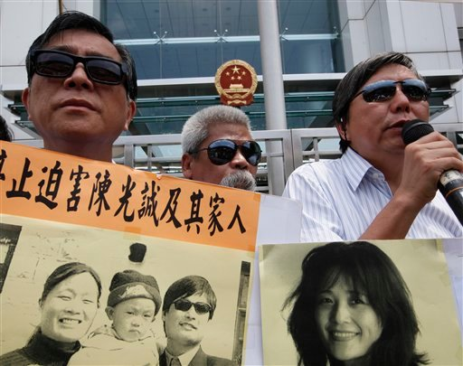 Pro-democracy protesters wearing sunglasses, hold placards with picture of blind Chinese legal activist Chen Guangcheng, third left, with his family and Chinese activist He Peirong, right, outside the China's Liaison Office in Hong Kong Monday, April 30