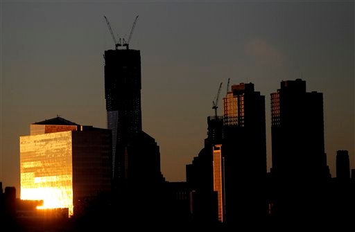 The sun reflects on a building as it rises Monday April 30, 2012, including One World Trade Center, center left, in New York as seen from Jersey City, N.J. (AP Photo/Julio Cortez)