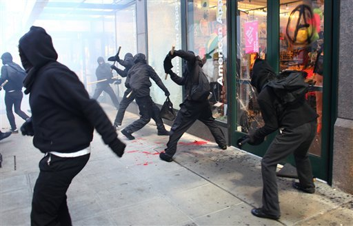 Protesters break windows on downtown businesses including American Apparel and NikeTown during a May Day rally on Tuesday, May 1, 2012 in downtown Seattle. (AP Photo/Seattlepi.com, Joshua Trujillo)