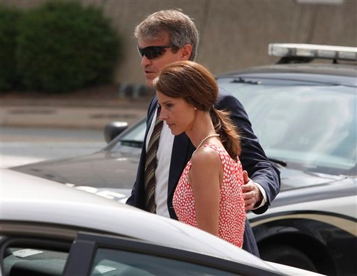 Cheri Young, right, is escorted out of the Federal Courthouse in Greensboro, N.C. on Monday, April 30, 2012, after testifying in the John Edwards trial.