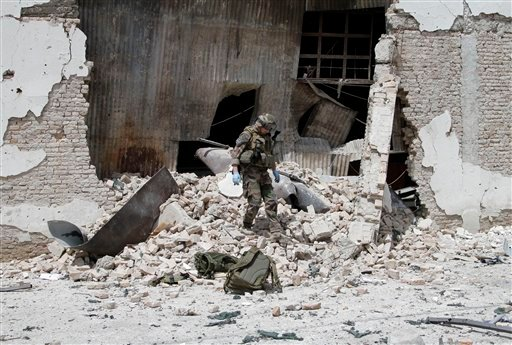 A French soldier part of the NATO forces walks on debris after the compound was attacked by militants in Kabul, Afghanistan, Wednesday, May 2, 2012. (AP Photo/Ahmad Jamshid)
