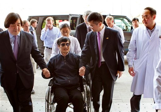 In this photo released by the US Embassy Beijing Press Office, blind lawyer Chen Guangcheng is wheeled into a hospital by U.S. Ambassador to China Gary Locke, right, and an unidentified official at left, in Beijing Wednesday May 2, 2012.