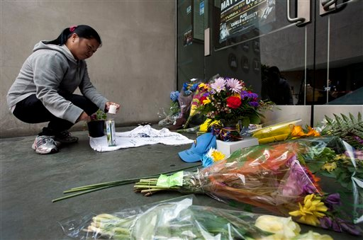 Gemma Estenol lights a candle to leave in front of the doors of former NFL football player Junior Seau's restaurant, Wednesday, May 2, 2012, in San Diego.