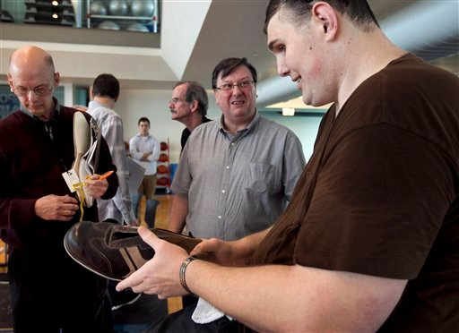 Igor Vovkovinskiy, of Minneapolis, right, currently the tallest man in the United States at seven feet eight inches, speaks with Trevor Kirby, center, a shoe engineer, at Reebok headquarters, in Canton, Mass., Thursday, May 3, 2012. (AP Photo)