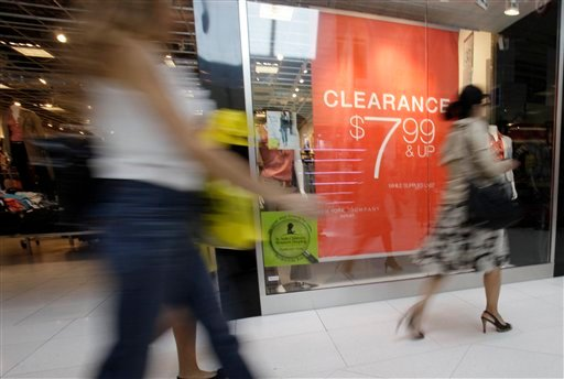In this Nov. 9, 2011 file photo, shoppers walk past a clearance sign at the New York & Company outlet store at the Dolphin Mall, in Miami. (AP Photo/Lynne Sladky, File)