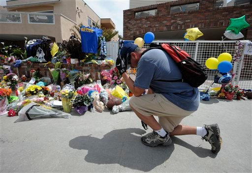 San Diego Chargers fan Dennis Telles bows down in front of a memorial in the driveway of the house of former NFL star Junior Seau.