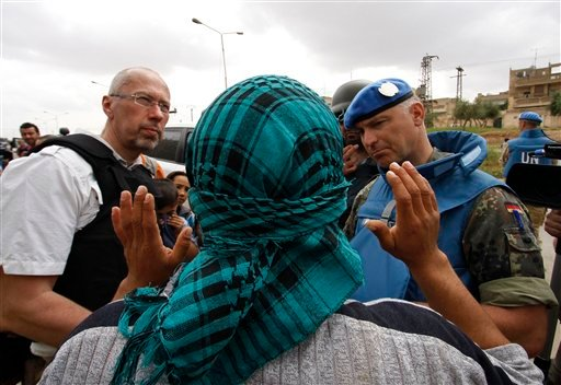 In this picture taken during UN observer-organized media tour, a Syrian man, who covers his face to obscure his identity, speaks to UN observers about conditions in Hama city, central Syria, on Thursday May 3, 2012. (AP)