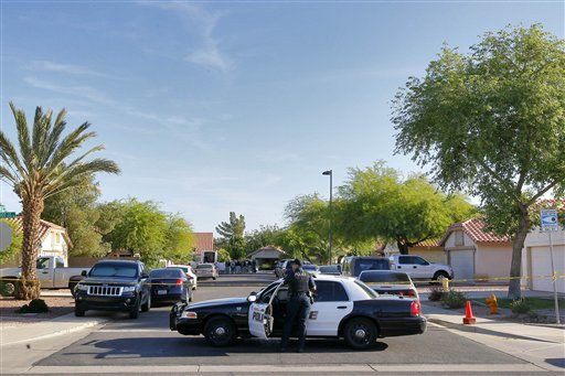 A Gilbert police officer blocks the street outside a shooting crime scene Thursday, May 3, 2012 in Gilbert, Ariz. (AP Photo/Matt York)