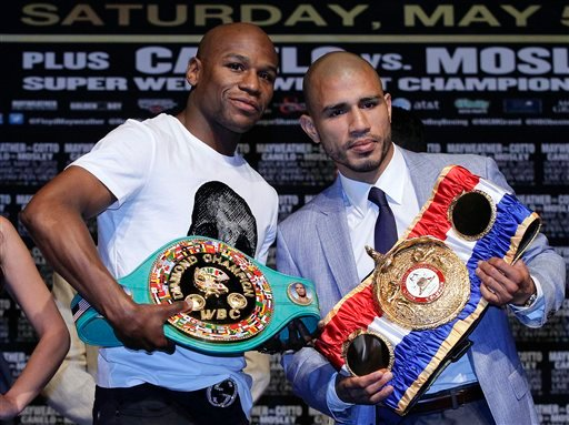 Floyd Mayweather, left, and Miguel Cotto pose for a photo during a news conference Wednesday, May 2, 2012, in Las Vegas.