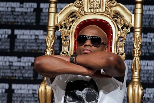 Floyd Mayweather stretches in his seat while waiting to speak during a news conference Wednesday, May 2, 2012, in Las Vegas.