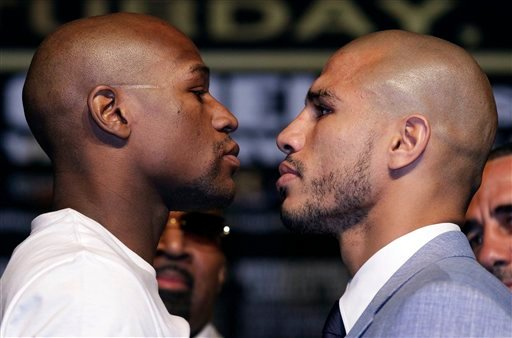 Floyd Mayweather Jr., left, and Miguel Cotto pose for a photo during a news conference.