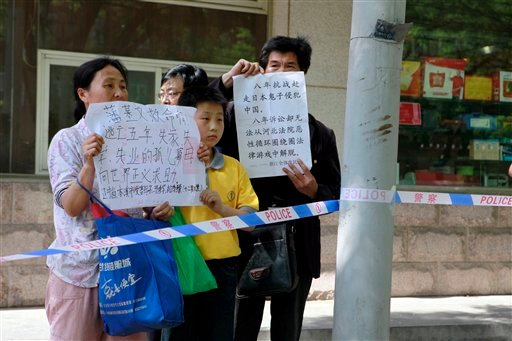 Chinese petitioners hold up papers to protest their own grievances outside the hospital where blind activist lawyer Chen Guangcheng is recuperating in Beijing, Saturday, May 5, 2012. (AP)