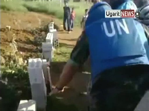 In this image made from amateur video released by Ugarit News and accessed Saturday, May 5, 2012, a U.N. observer, right, inspects what residents of the town of Taftanaz, Syria, tell him is a mass grave. (AP)