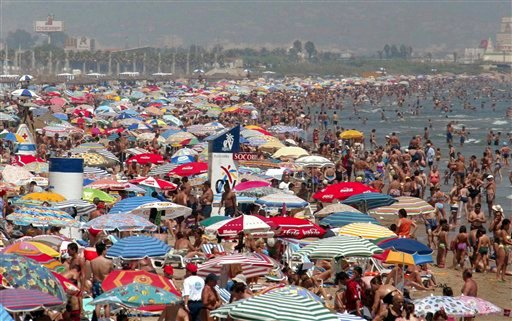 FILE - in this Thursday Aug. 7, 2003 file photo crowds flock to a beach in Valencia in south eastern Spain at the beginning of the traditional August summer holidays. (AP Photo/Ramon Espinosa, file)