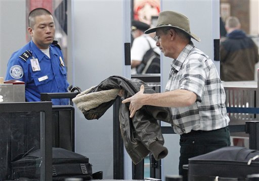 This April 30, 2012, photo shows a traveler passing through a security check point at Portland International Airport, in Portland, Ore. (AP Photo/Rick Bowmer)