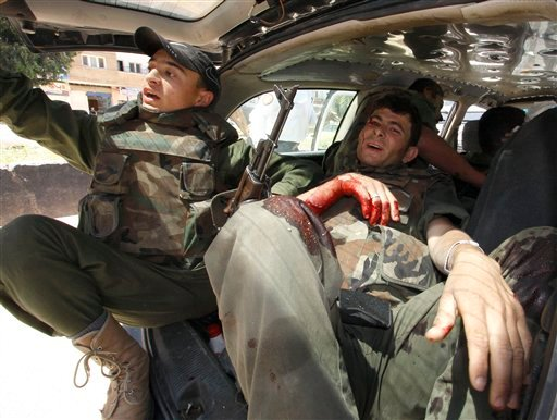 A Syrian army injured soldier, right, who was wounded after a roadside bomb hit his military truck, is seen carried by another vehicle to a hospital, in Daraa city, southern Syria, on Wednesday May 9, 2012.