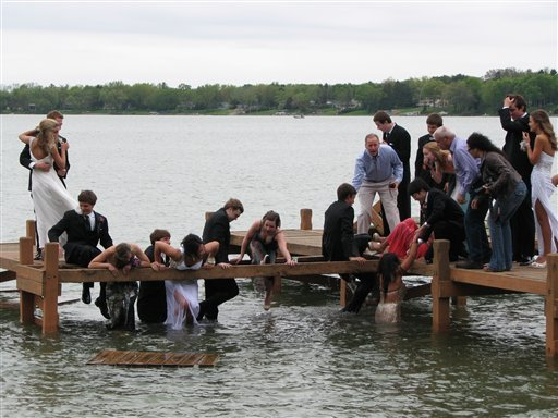 A group of Wisconsin high school students make their way out of the waist-deep water after a pier they were posing for photos on prior to their prom collapsed, sending about half of the 18 students on the pier into a lake, in Oconomowoc, Wis. on May 5.
