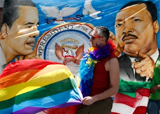 Trenton Garris waves his rainbow flag in front of a banner in support of President Barack Obama who was visiting the Paramount Theater one day after announcing his support for same sex marriage, in Seattle on Thursday, May 10, 2012. (AP Photo/Kevin P. Cas