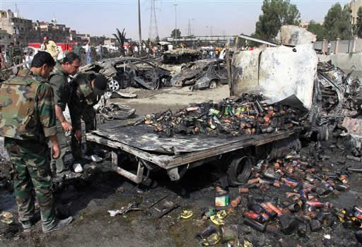 Syrian soldiers check a burned truck in front of a damaged military intelligence building where two bombs exploded, at Qazaz neighborhood in Damascus, Syria, on Thursday May 10, 2012. (AP Photo/Bassem Tellawi)