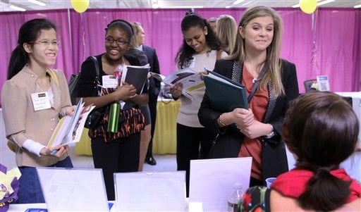 In this April 4, 2012 photo, Martina Ryberg, right, of Plymouth State University, talks with Tara Rossetti, of On Call International, during a job fair for college students in Manchester, N.H. (AP Photo/Jim Cole)