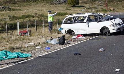 Policemen examine the scene of a minivan crash near Turangi, New Zealand, Saturday, May 12, 2012. (AP Photo/New Zealand Herald, John Cowpland)