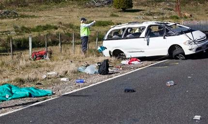 Policemen examine the scene of a minivan crash near Turangi, New Zealand, Saturday, May 12, 2012. (AP Photo/New Zealand Herald, John Cowpland)